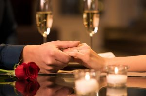 couple holding hand across table with candles, champagne, and rose