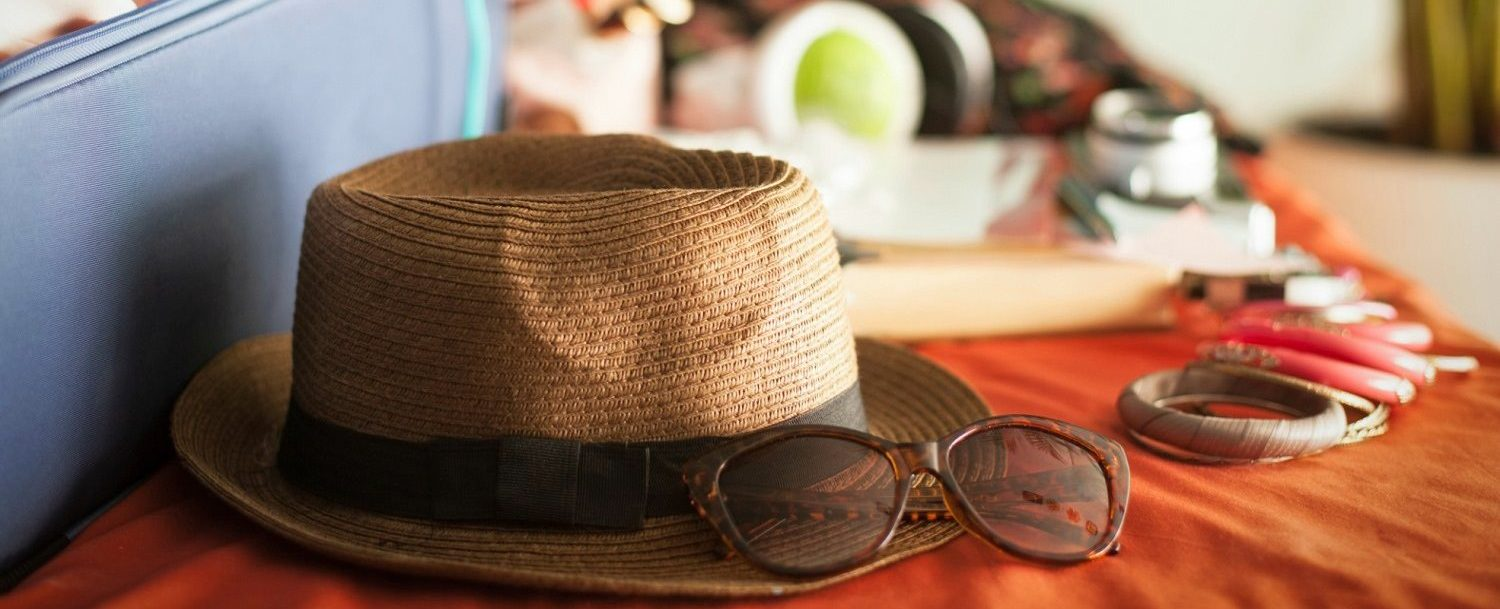 hat and sunglasses on bed while packing for vacation