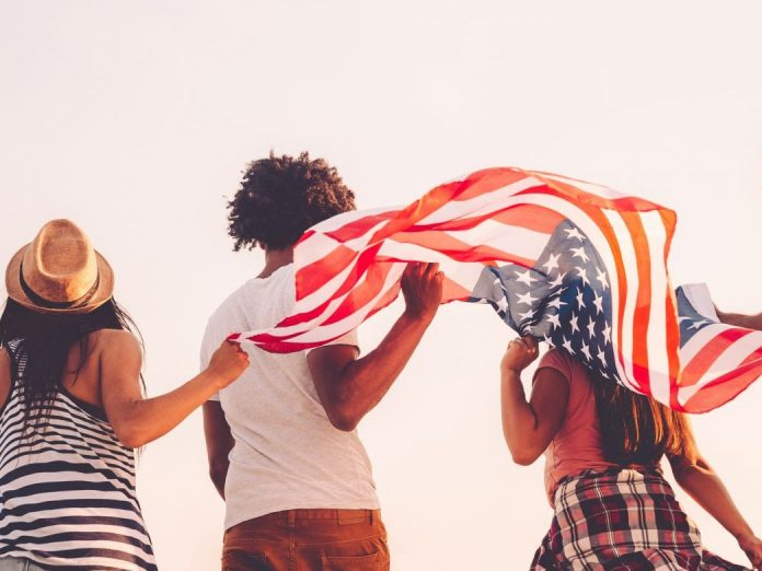 Rear view of four young people carrying american flag while running outdoors Jackson, MS, Fourth of July events