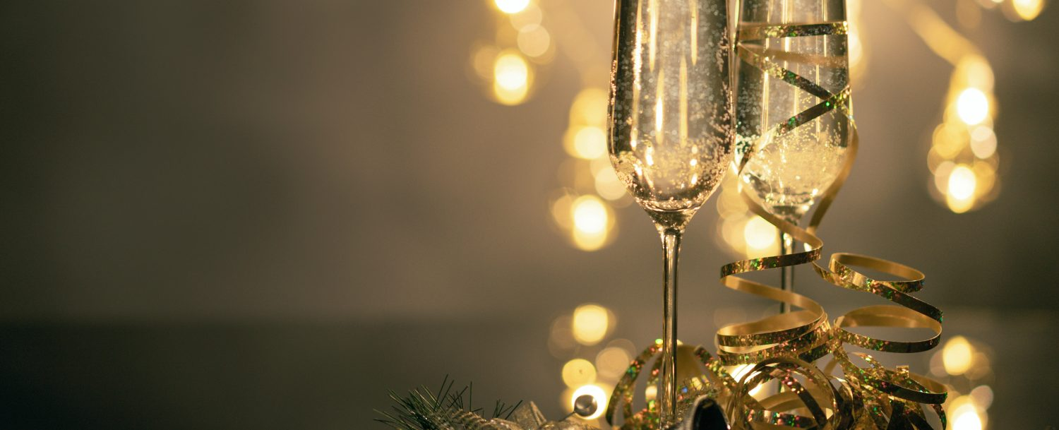 two champagne glasses with new year's eve confetti