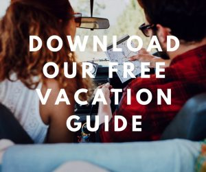 "Couple in car looking at map with overlaying text ""download our free Vacation Guide"""