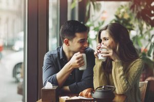 couple smiling at each other while sipping coffee
