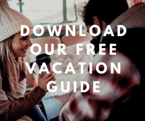 "Couple drinking coffee and looking at a map in the winter with overlaying text saying ""download our free Vacation guide"""