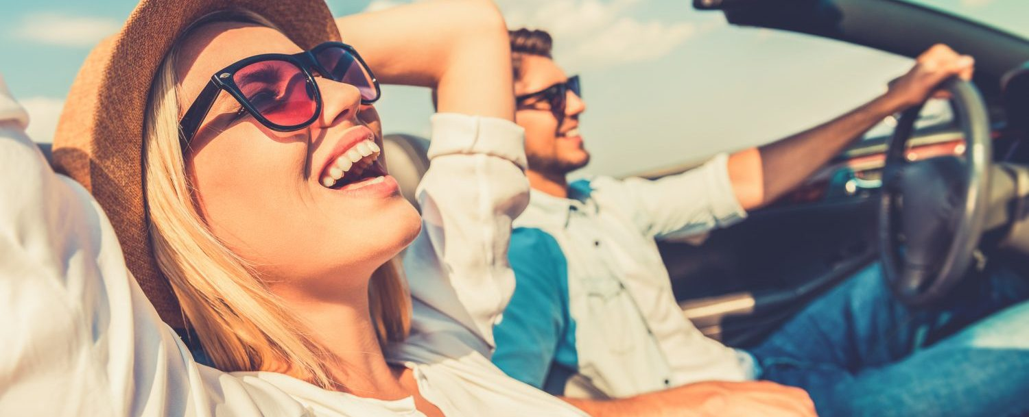 couple smiling while riding with the top down on a car during road trip