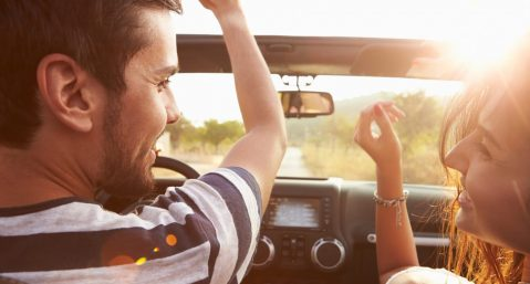 Young Couple Driving Along Country Road In Open Top Car on a trip to visit the best cities in the South