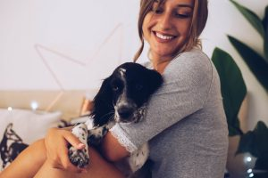 Woman cuddling with her puppy on a bed | Pet-Friendly accommodations