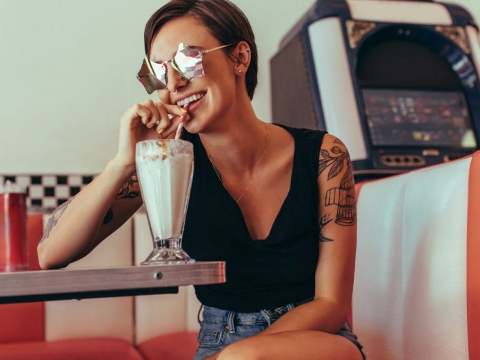 Smiling woman drinking milkshake with a straw sitting at Brent's Drugs