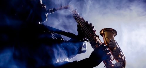 jazz musician playing the saxophone in a club where you can listen to live music in Jackson, MS
