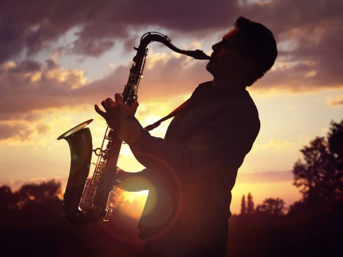 Saxophone player or saxophonist performing sax against sunset along the Mississippi Blues Trail