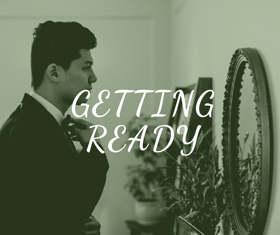 """""""Getting Ready"""" text over photo of groom looking in the mirror"""