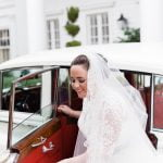 smiling bride getting out of vintage car