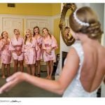 bridal party smiling at seeing bride in her dress