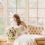 bride posing on couch by window