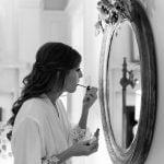 grayscale bride applying lip stick in mirror