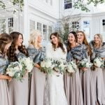 bridal party smiling at bride outdoors