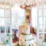 wedding cake with green and pink flowers