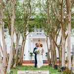 bride and groom kissing in front of Fairview Inn