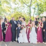 wedding party smiling while bride and groom kiss