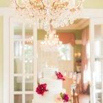 wedding cake with pink flowers under chandelier