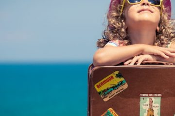 girl leaning on suitcase looking up at the beach