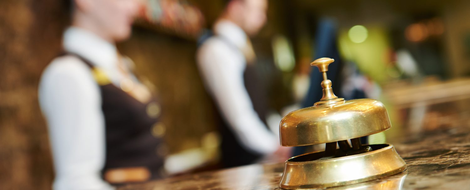 close up concierge bell with blurred employees in background